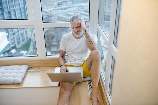 Interessant hier. lächelnder grauhaariger bärtiger mann mit tattoos in shorts und t-shirt mit laptop zu hause auf der fensterbank tagsüber