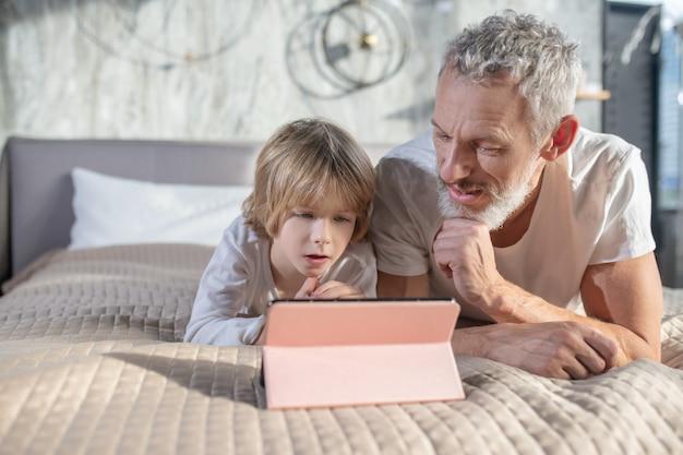 Interessante beschäftigung. fokussiertes kind mit grauhaarigem vater in der hauskleidung, die interessiert auf tablette zu hause auf dem bett schaut