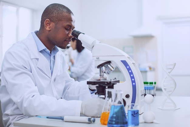Interessante forschung. konzentrierter erfahrener wissenschaftler, der mit seinem mikroskop arbeitet und eine uniform trägt