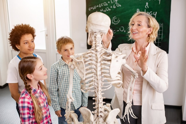 Interessante lektion. erfreuter kluger lehrer, der auf das skelett zeigt, während er über menschliche knochen spricht