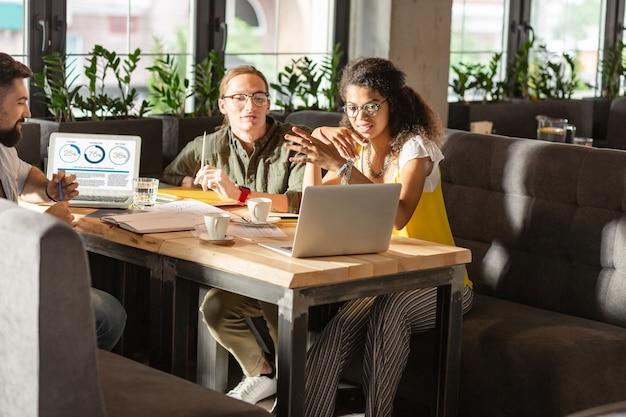 Interessante präsentation. nette kluge leute, die auf den laptop-bildschirm schauen, während sie eine interessante präsentation überprüfen checking
