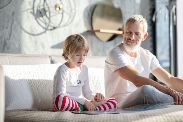 Interessante tätigkeit. beteiligtes kind, das buch und seinen lächelnden vater liest, der zu hause auf dem bett sitzt