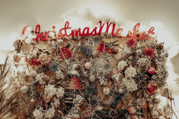 Interessante und kreative weihnachtswand verziert mit spielzeugbällen und goldenen dekorationen des neuen jahres