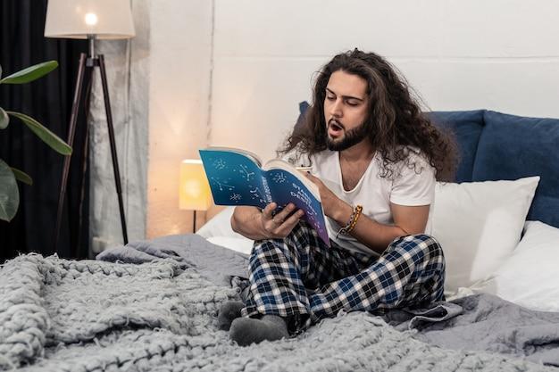 Interessante wissenschaft. angenehmer schläfriger mann, der ein buch liest, während er ernsthaft astrologie studiert studying