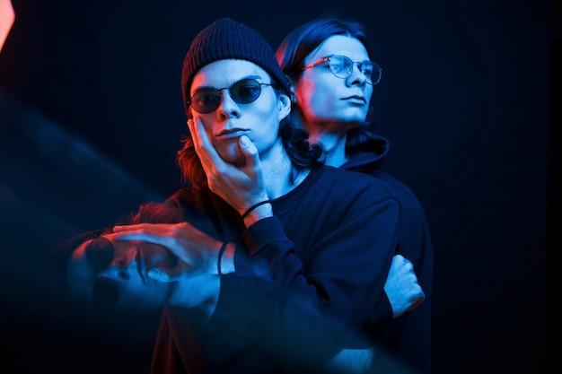 Interessanter effekt. porträt von zwillingsbrüdern. studioaufnahme im dunklen studio mit neonlicht