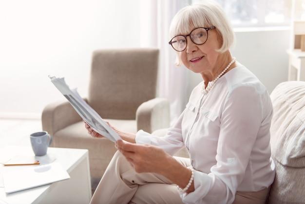 Interessanter inhalt. angenehme ältere frau in brillen, die eine zeitung lesen und auf der couch im wohnzimmer sitzend aufwerfen