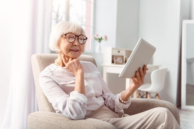 Interessantes buch. fröhliche hübsche ältere frau, die in einem bequemen sessel im wohnzimmer sitzt und von einer tafel liest