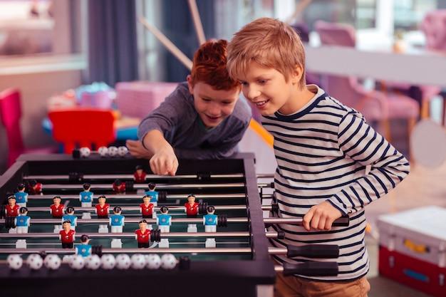 Interessantes spiel. fröhlicher blonder junge, der in der halbstellung steht und kickerfußball betrachtet