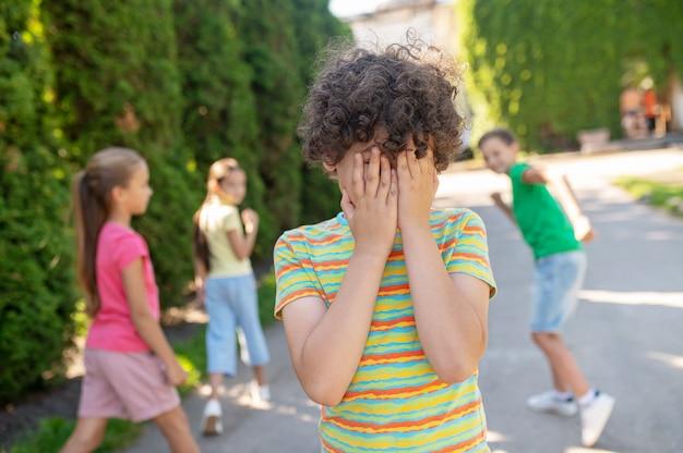 Interessantes spiel. grundschulkinder in freizeitkleidung spielen am sommertag im park verstecken