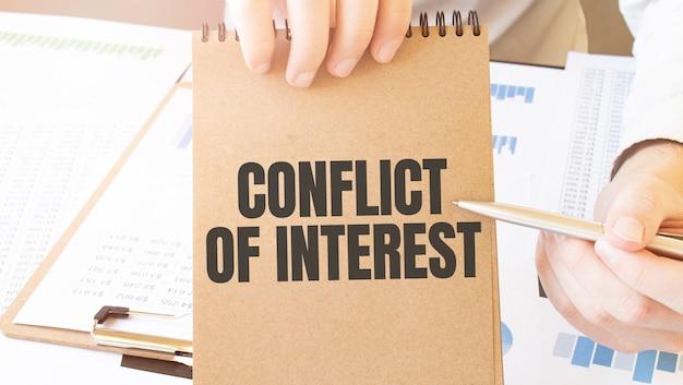 Interessenkonflikt des textes auf notizblock des braunen papiers in geschäftsmannhänden auf dem tisch mit diagramm