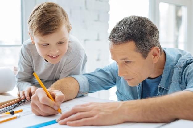 Interessiert an arbeit. ein fröhlicher teenager sitzt am tisch im büro seines vaters und sieht zu, wie sein vater eine blaupause zeichnet, die sich ganz auf den prozess konzentriert