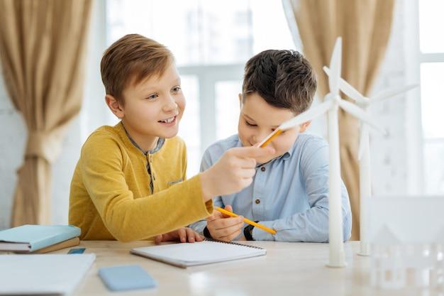 Interessiert an wissenschaft. neugieriger jugendlicher junge, der am tisch im büro ihres vaters sitzt und windturbinen untersucht, bevor er sie zeichnet