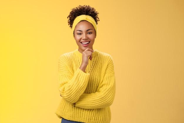 Interessierte aufgeregt begeisterte gut aussehende unternehmerin stilvolle pullover stirnband afro-frisur, die das kinn berührt, nachdenklich lächelnd, die projektidee mag, die auf gelbem hintergrund steht, fasziniert.