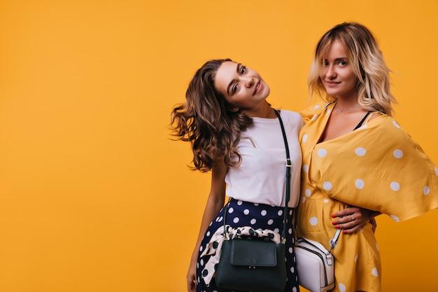Interessierte brünette frau mit stilvoller handtasche, die nahe freund auf gelb steht. wunderschöne kaukasische dame im orangefarbenen kleid