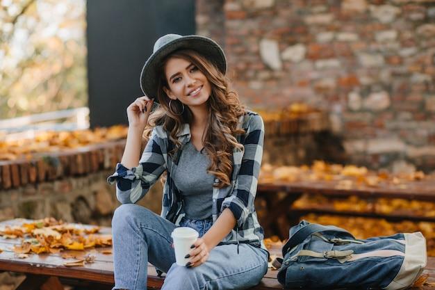 Interessierte dame mit eleganter schwarzer maniküre trinkt kaffee auf holzbank mit goldenen blättern auf hintergrund