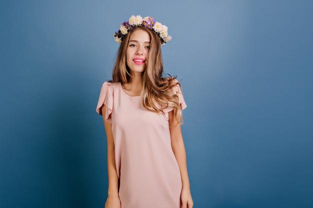 Interessierte europäische frau im eleganten rosa kleid, das im studio aufwirft