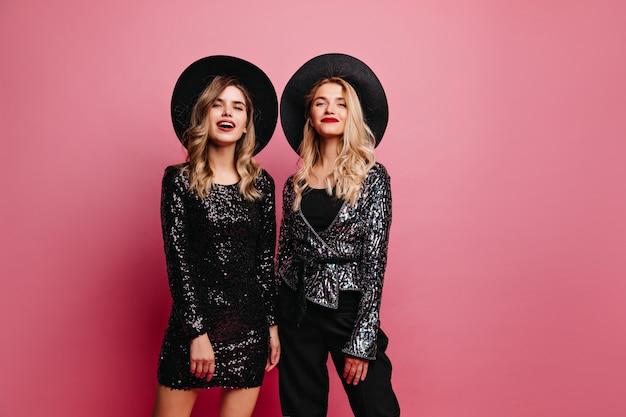 Interessierte frau in glänzenden kleidern, die auf party warten. elegante junge damen in hüten.