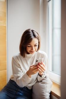 Interessierte hübsche teenagerfrau im weißen t-shirt mit smartphone-sms