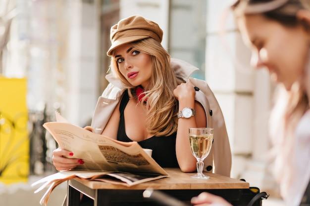 Interessierte junge frau, die sich umsieht, zeitung hält und wein trinkt. außenporträt des reizenden mädchens trägt kappe und stilvollen beige mantel am kalten tag während der ruhe im café.