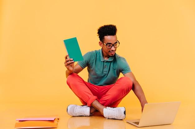 Interessierter afrikanischer student in den gläsern, die mit lehrbüchern auf dem boden sitzen. männlicher freiberufler in hellen kleidern mit laptop.