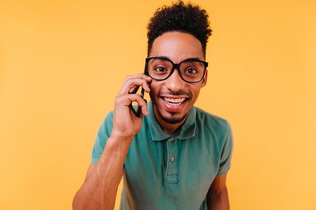 Interessierter dunkeläugiger mann in brille, der am telefon spricht. glücklicher afrikanischer kerl trägt grüne kleidung, die mit smartphone aufwirft.