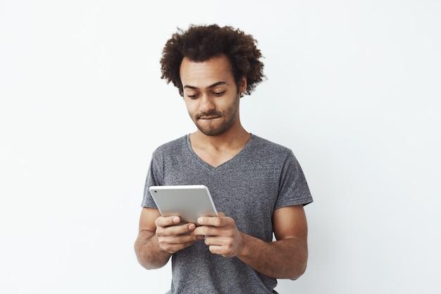 Interessierter und konzentrierter junger afrikanischer mann, der tablette betrachtet, die ein plattformer-spiel spielt und neue niveaus über weißem bakground genießt.