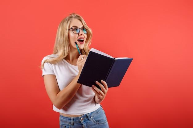 Interessiertes blondes mädchen in den gläsern, die notizbuch und stift halten. notizen machen.