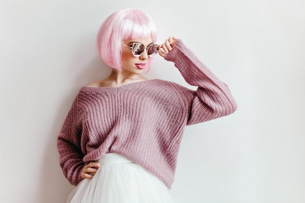 Interessiertes kaukasisches mädchen im lila pullover und im weißen rock, die nahe wand stehen. entzückende junge frau in der rosa perücke und in der sonnenbrille, die auf lichtwand aufwirft.