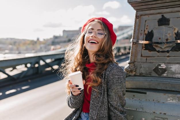 Interessiertes kaukasisches mädchen im weinlese-outfit, das kaffee während der reise durch europa trinkt