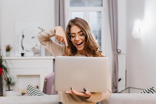 Interessiertes mädchen mit trendiger maniküre, die zu hause während des fotoshootings mit laptop herumalbert