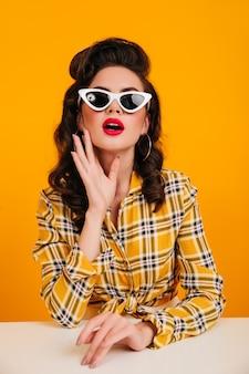 Interessiertes pinup-mädchen, das in eleganter sonnenbrille aufwirft. studioaufnahme der bezaubernden braunhaarigen dame im karierten hemd.