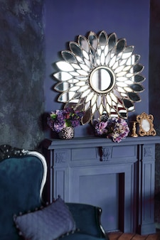 Interieur des modernen art-deco-wohnzimmers. luxus-interieur mit großem spiegel über kamin, blumen und klassischem sofa