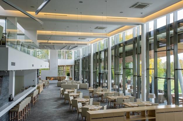 Interieur des modernen luxuriösen restaurants in einem großen business center mit zwei tischreihen, umgeben von stühlen und mehreren sofas zum ausruhen