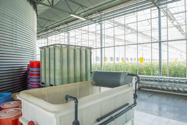 Interieur und ausstattung mit rohrleitungen und wassertank im modernen gewächshaus