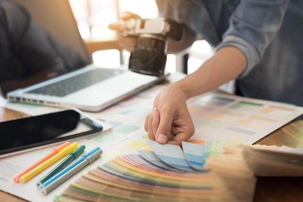 Interior design und renovierung und technologie-konzept - grafik-designer wählen richtige farbmuster für die auswahl auf dem tisch.