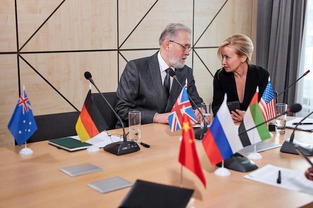 Interkulturelle delegierte diskutieren punkte ihrer kollegenrede, multiethnisches treffen im modernen sitzungssaal, alle in formeller kleidung, meinungen austauschen