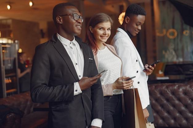 Internationale leute, die in einem café mit einkaufstüten stehen