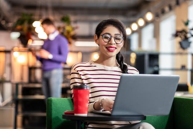 Internationale schönheit. nette weibliche person, die lächeln auf ihrem gesicht hält, während sie auf bildschirm des computers starrt