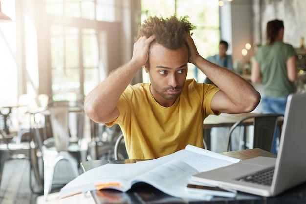 Internationaler afroamerikanischer student, der sich gestresst fühlt, die hände auf dem kopf hält und frustriert und verzweifelt auf den laptop-bildschirm starrt