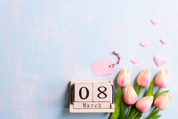 Internationaler frauentag konzept. rosa tulpen und papierherzen mit 8. märz text