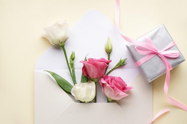 Internationaler frauentag. nahaufnahme umschlag mit eustomas, mit einer geschenkbox, flach liegen.