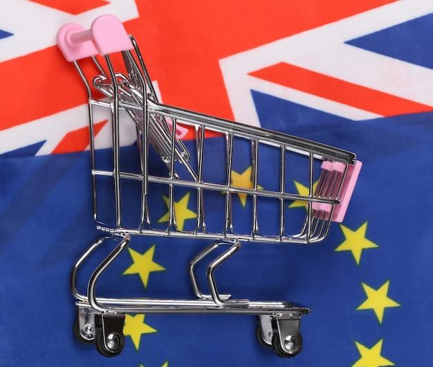 Internationaler, globaler supermarkt. mini-einkaufswagen auf dem hintergrund der verschwommenen flagge großbritanniens und der eurounion. shopping-konzept.