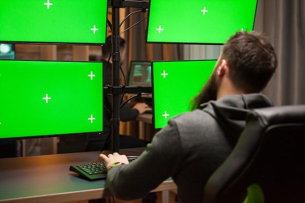 Internationaler hacker, der einen cyberangriff auf computer mit grünem chroma-key plant.