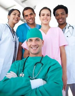 Internationales ärzteteam mit einem selbstbewussten chirurgen im vordergrund