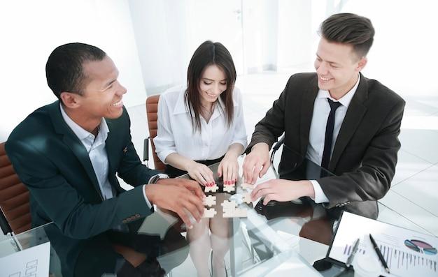 Internationales business-team beim zusammenstellen von puzzles im büro. das konzept der teamarbeit