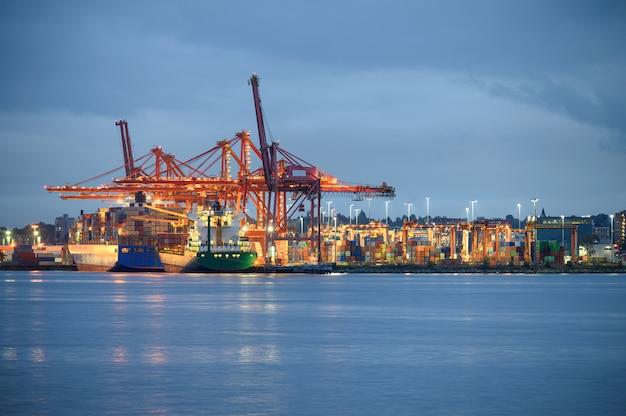 Internationales frachtschiff mit containerfrachtbeleuchtung und portalkranen am hafen