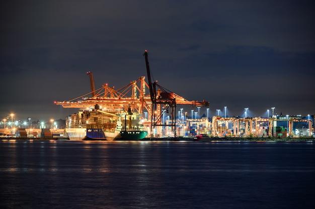 Internationales frachtschiff mit containerfrachtbeleuchtung und portalkranen im hafen