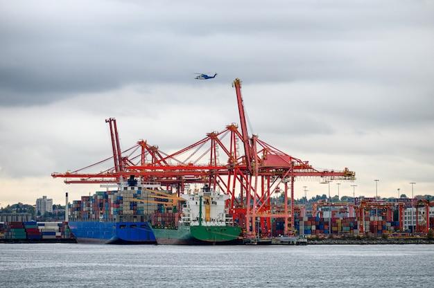 Internationales frachtschiff mit containern, kränen und hubschrauberfliegen