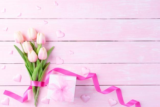 Internationales frauentagkonzept. rosa tulpen und rotes herz mit geschenkbox