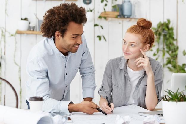 Internationales team von zwei kreativen mitarbeitern, die mit blaupausen am schreibtisch sitzen